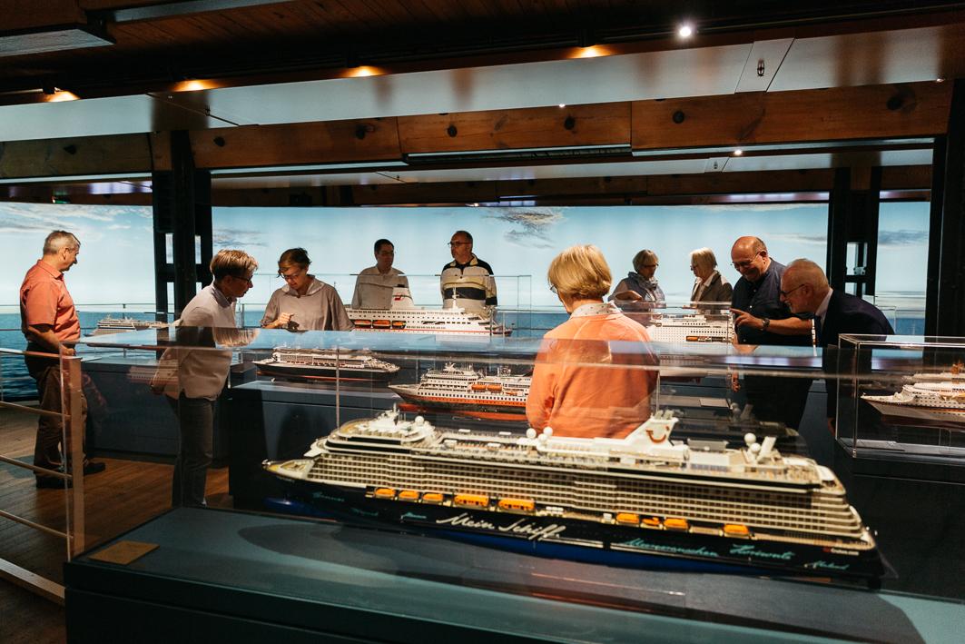 Ältere Menschen betrachten freudvoll Modelle von Kreuzfahrtschiffen im Besucher bei der Internationalen Maritimen Museum