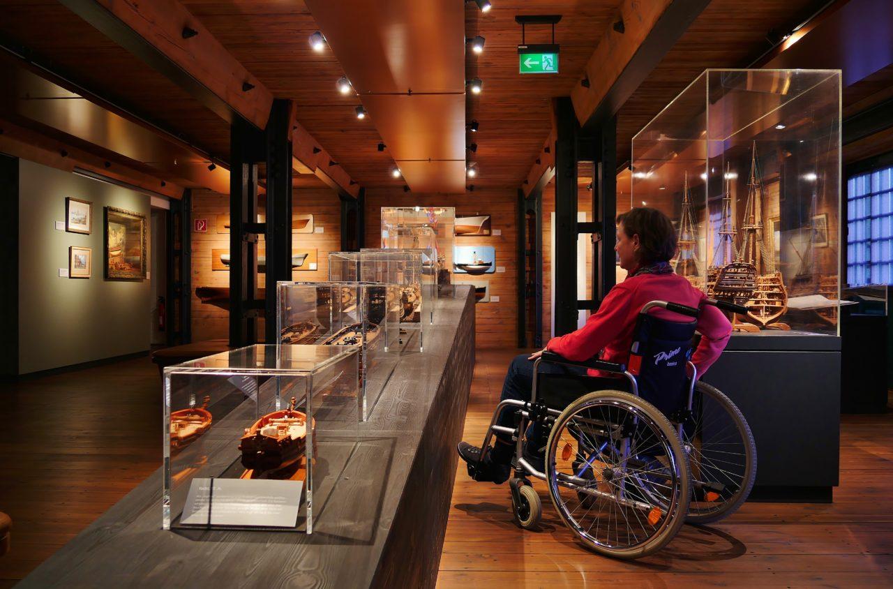 Frau im Rollstuhl betrachtet Objekte in Vitrinen des Internationalen Maritimen Museums. Copyright IMMH