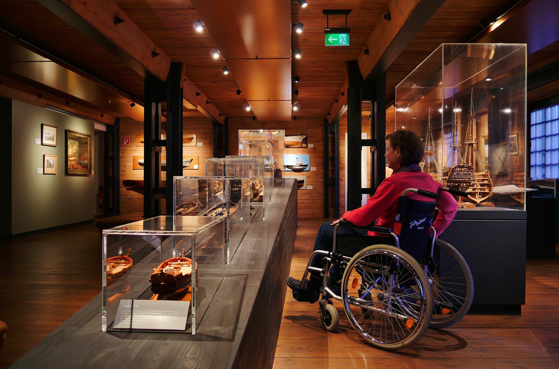 Frau im Rollstuhl betrachtet Objekte in Vitrinen des Internationalen Maritimen Museums