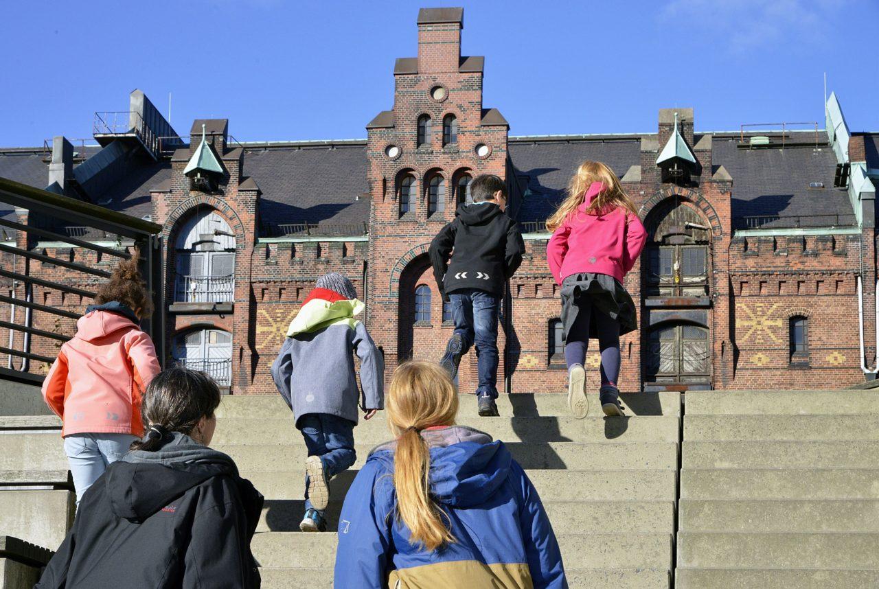 Rückansicht von Kindern, die vor blauem Himmel eine Treppe hochlaufen