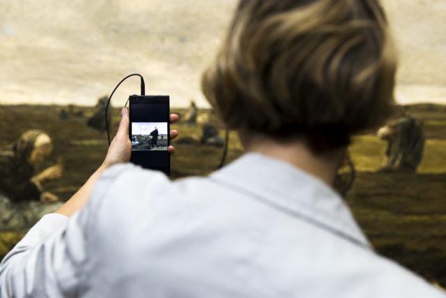 Eine Frau betrachtet ein Gemälde in der Hamburger Kunsthalle und lässt sich per Audioguide über das Werk erzählen