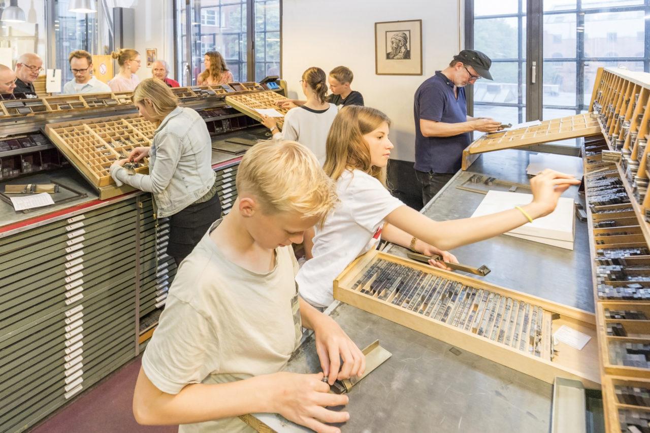 Eine Schulklasse setzt mit Bleilettern eine Drucksache im Museum der Arbeit. Copyright SHMH, Sinje Hasheider