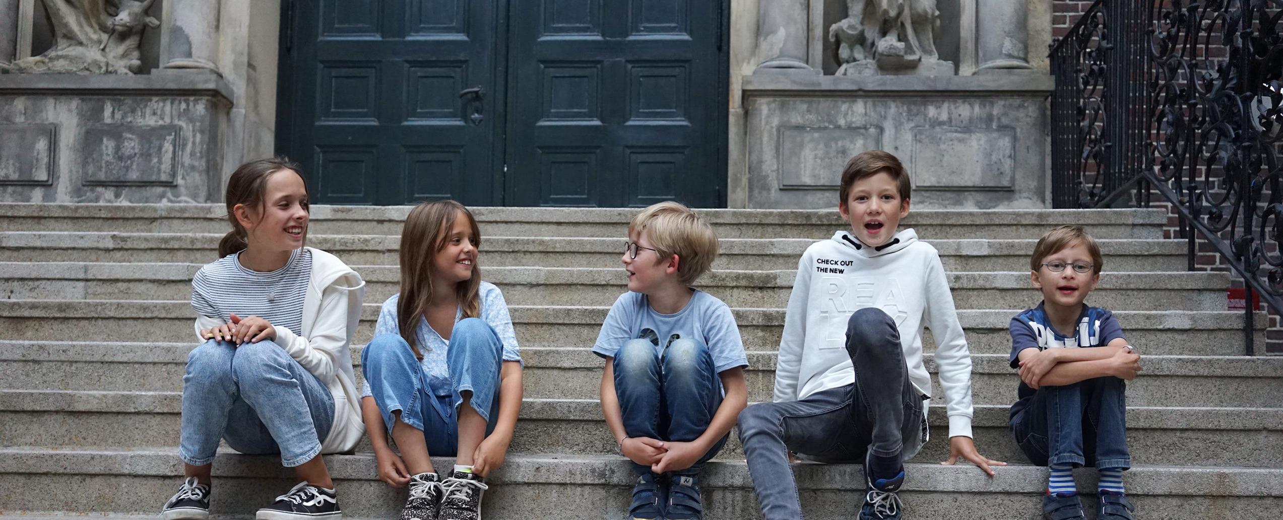 Kinder sitzen auf der Treppe im Innenhof des Museums für Hamburgische Geschichte