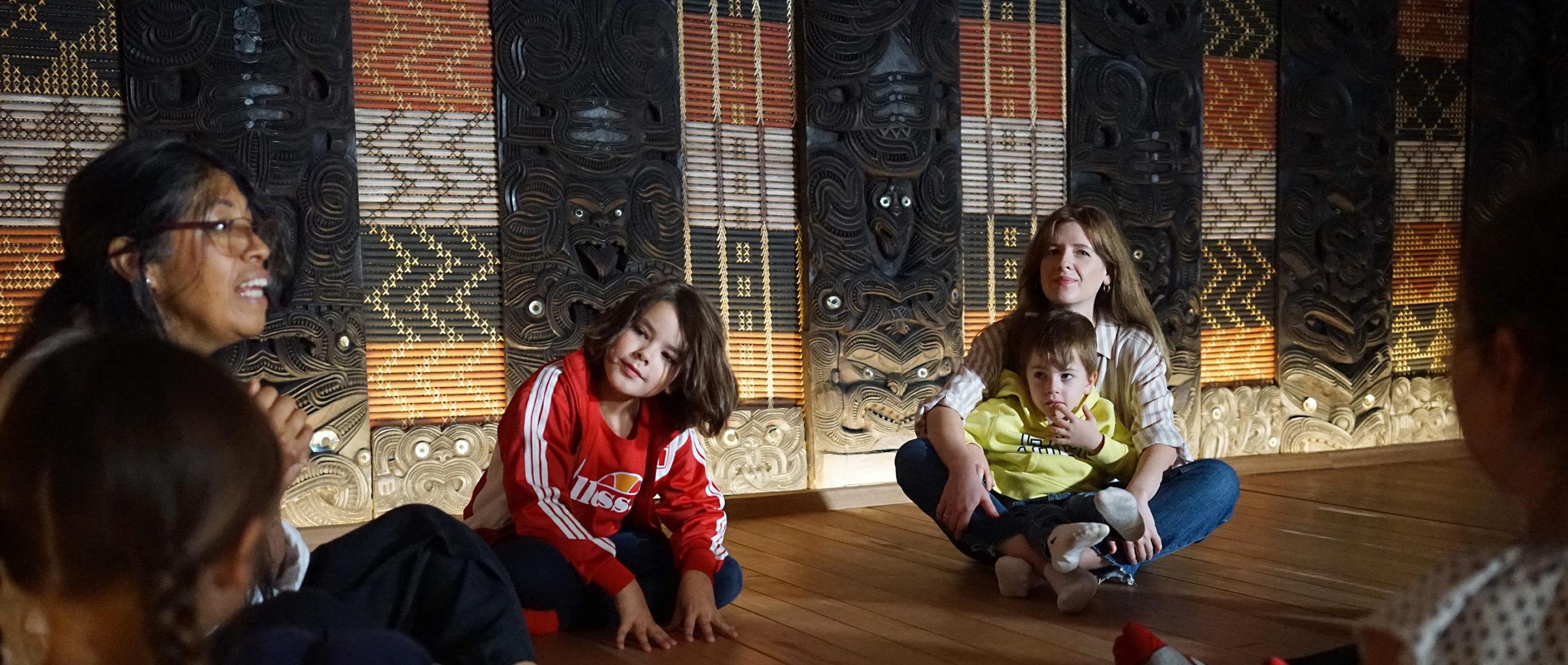 Kinder sitzen mit Müttern auf dem Boden im Maskensaal im MARKK und hören einer Guide zu