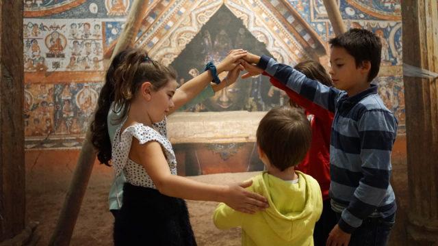 Kinder stehen im Ausstellungsbereich ALCHI im MARKK. Sie bilden mit ihren Armen ein Tor, durch das der kleinste geht