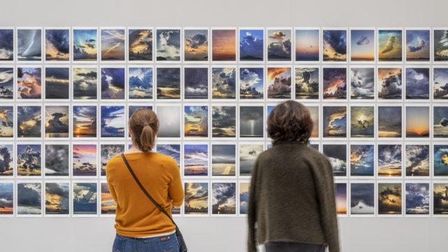In den Deichtorhallen betrachten zwei Frauen Fotografien von Michael Wolf, die Sonnenuntergänge zeigen