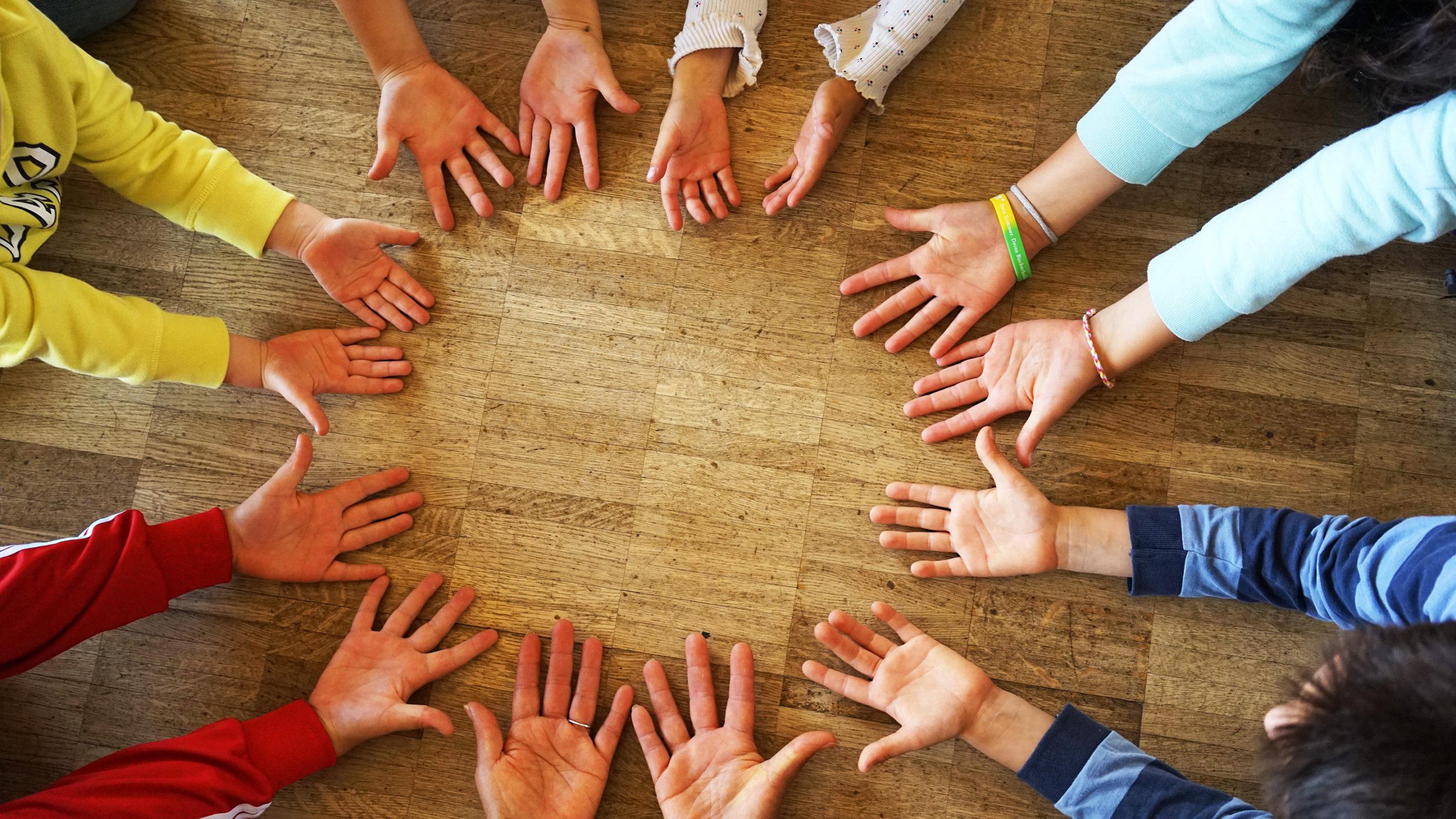Menschen bilden einen Kreis aus Händen mit offen ausgestreckten Handflächen