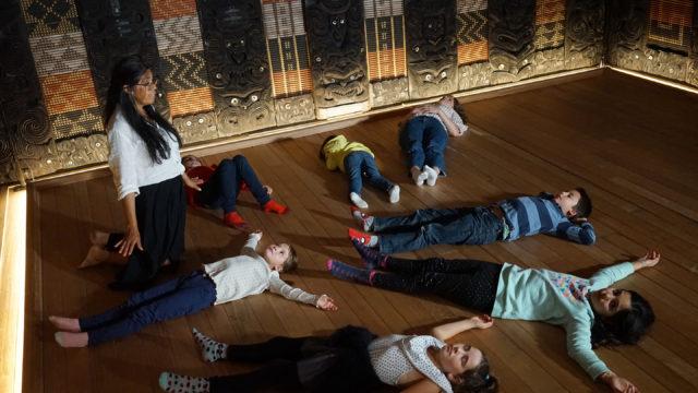 Kinder liegen auf dem Boden des Haus Rauru im MARKK. Ein Guide leitet sie zu einer Fantasiereise an