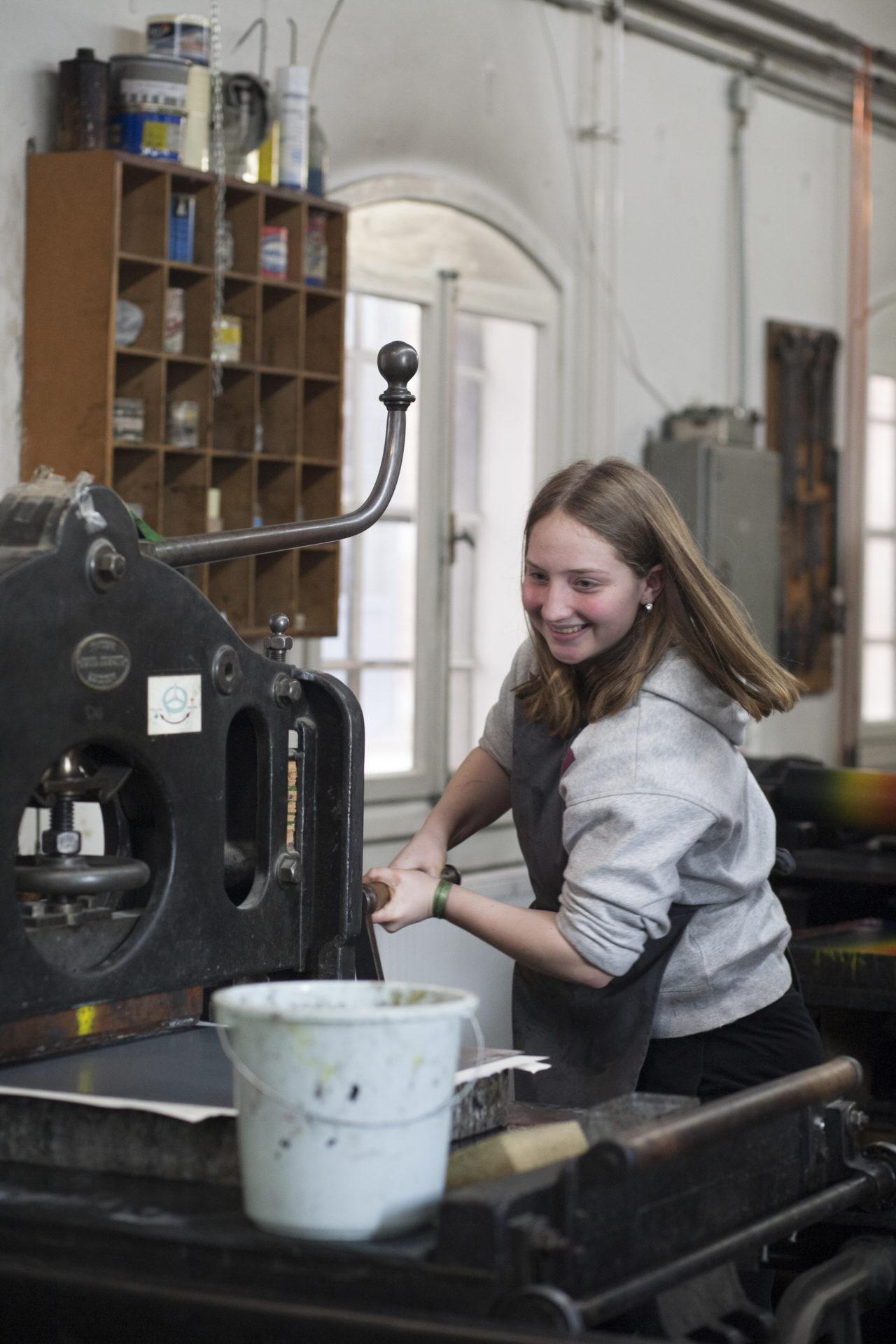 """Mädchen bedient mit Freude kraftvoll eine Steindruckpresse. Sie ist eine Teilnehmerin an einem """"Kultur macht stark!""""-Ferienprogramm im Museum der Arbeit. Copyright Museumsdienst Hamburg, Pia Schmikl, Muriel Borchert"""