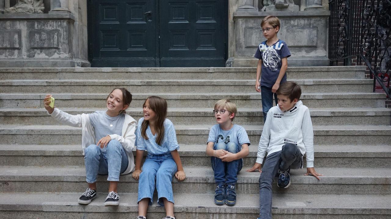 Kinder machen Selfies auf der Treppe im Innenhof des Museums für Hamburgische Geschichte