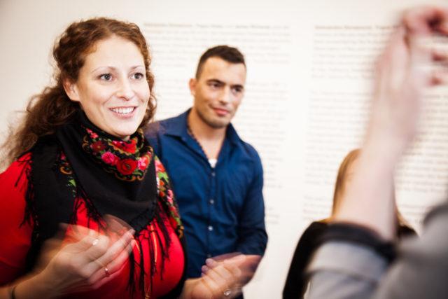 Eine lächelnde Frau gestikuliert bei einer Museumsführung