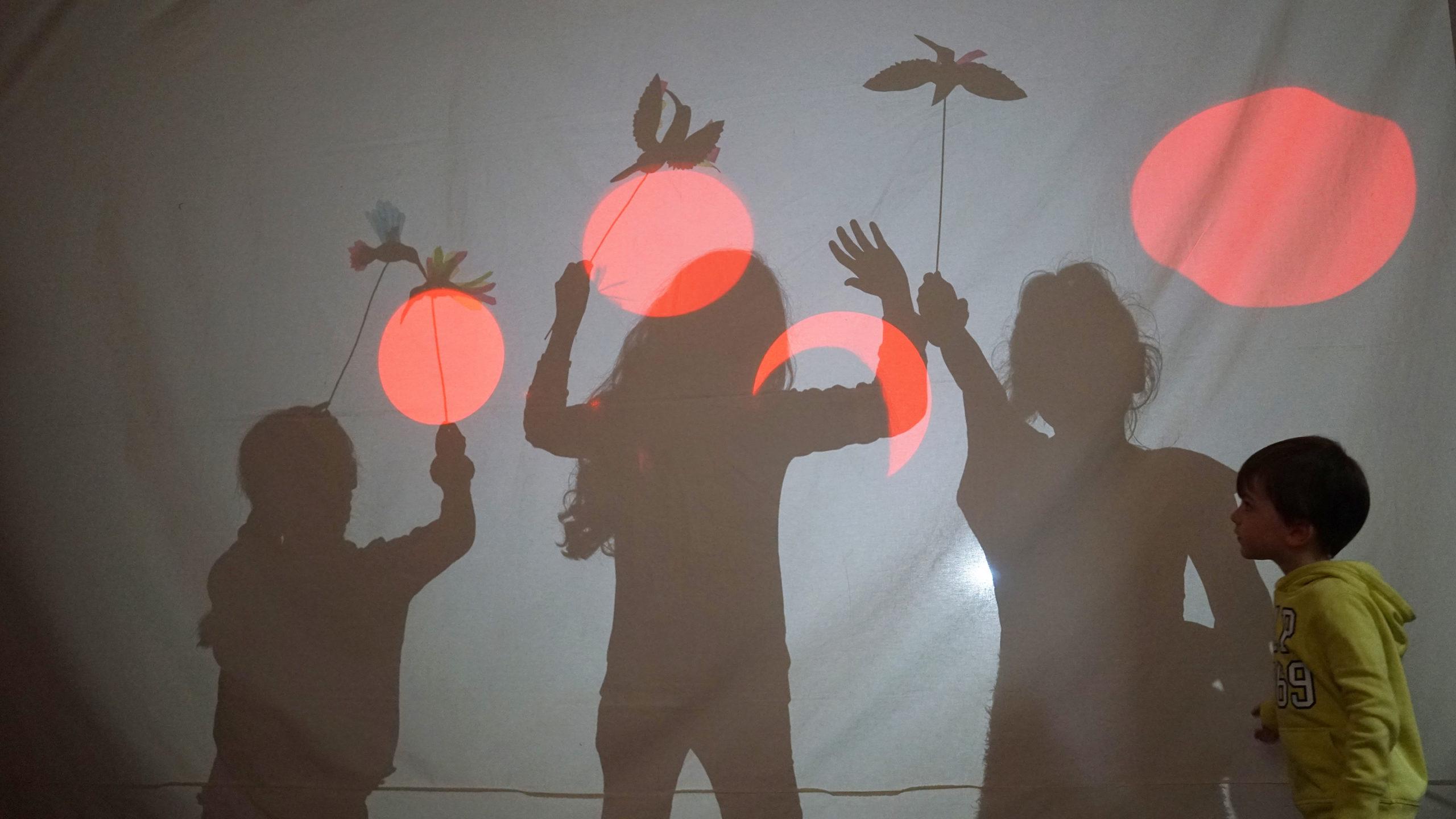 Kinder führen ein Schattenspiel im MARKK im Rahmen eines Vermittlungsangebotes auf