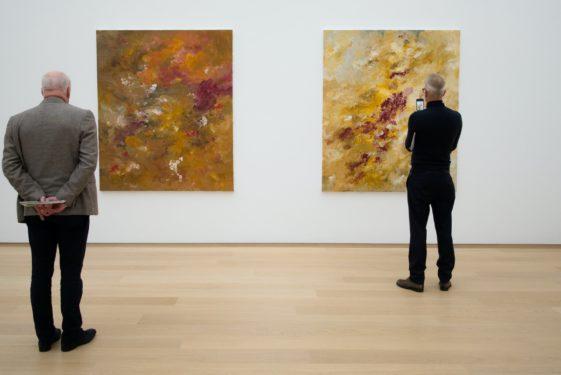 Ältere Männer betrachten abstrakte großformatige Bilder