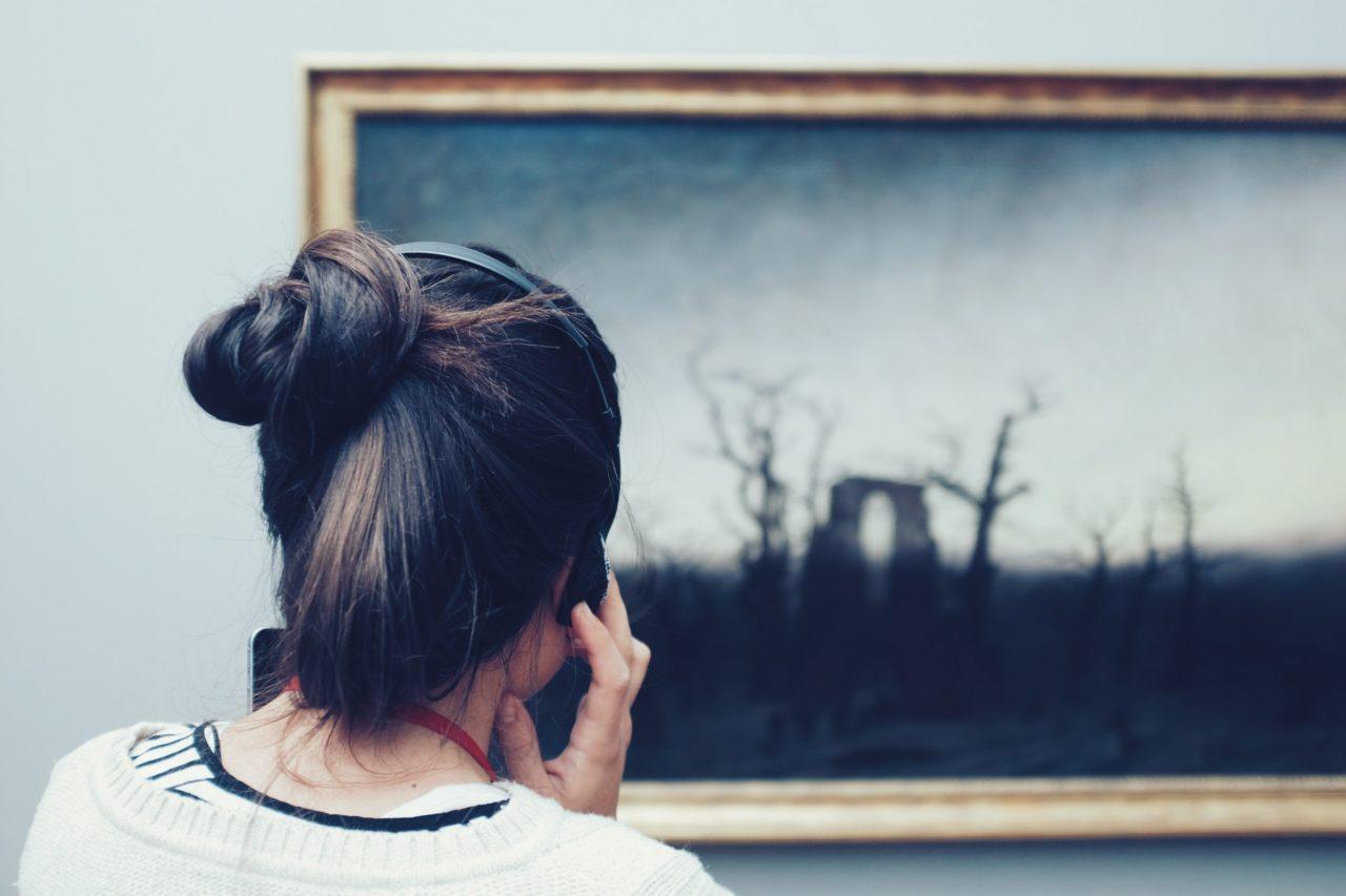 Eine Frau betrachtet ein Bild und presst sich dabei Kopfhörer ans Ohr