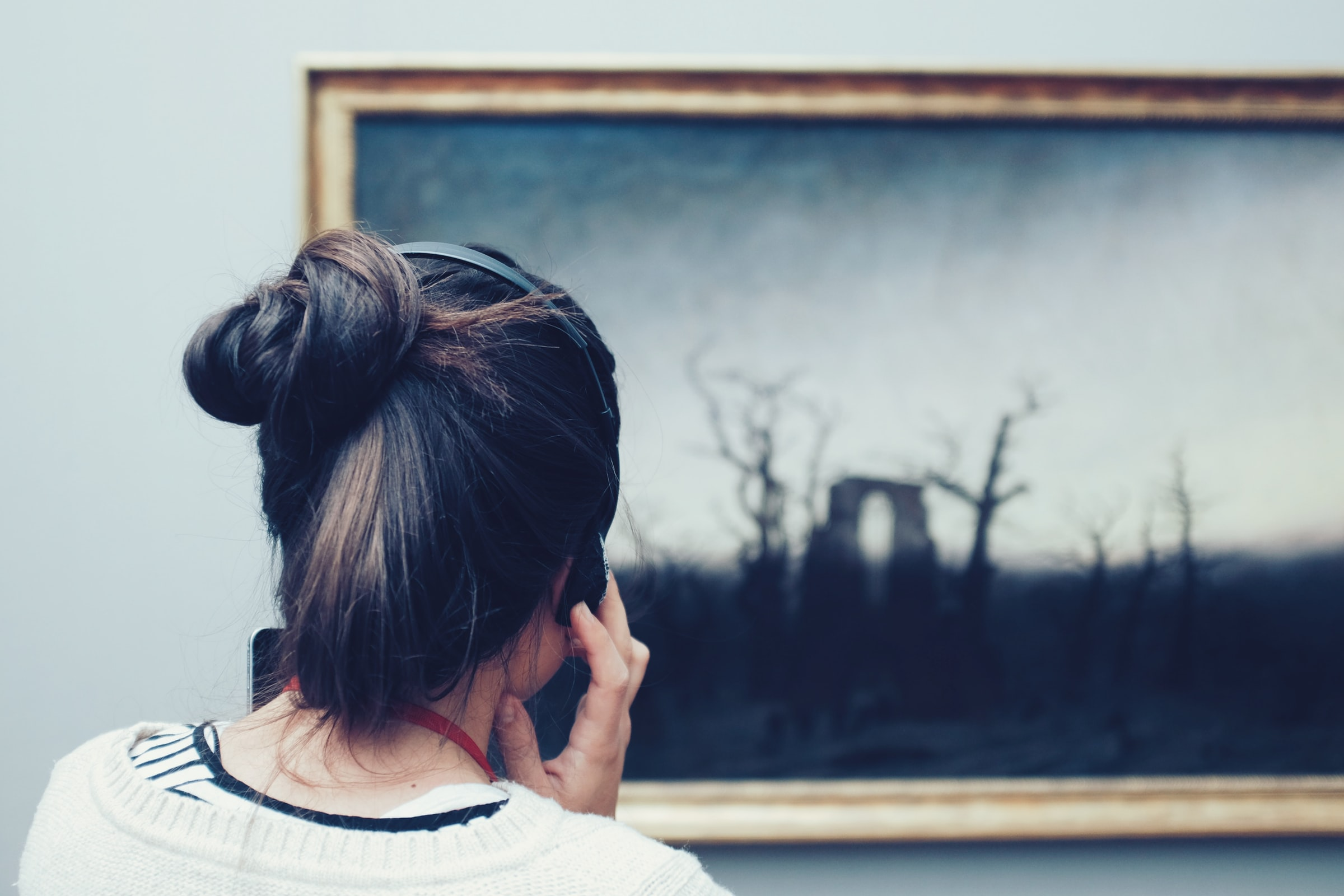 Eine Frau betrachtet ein Bild und presst sich dabei Kopfhörer ans Ohr. © Mike Kotsch, Unsplash