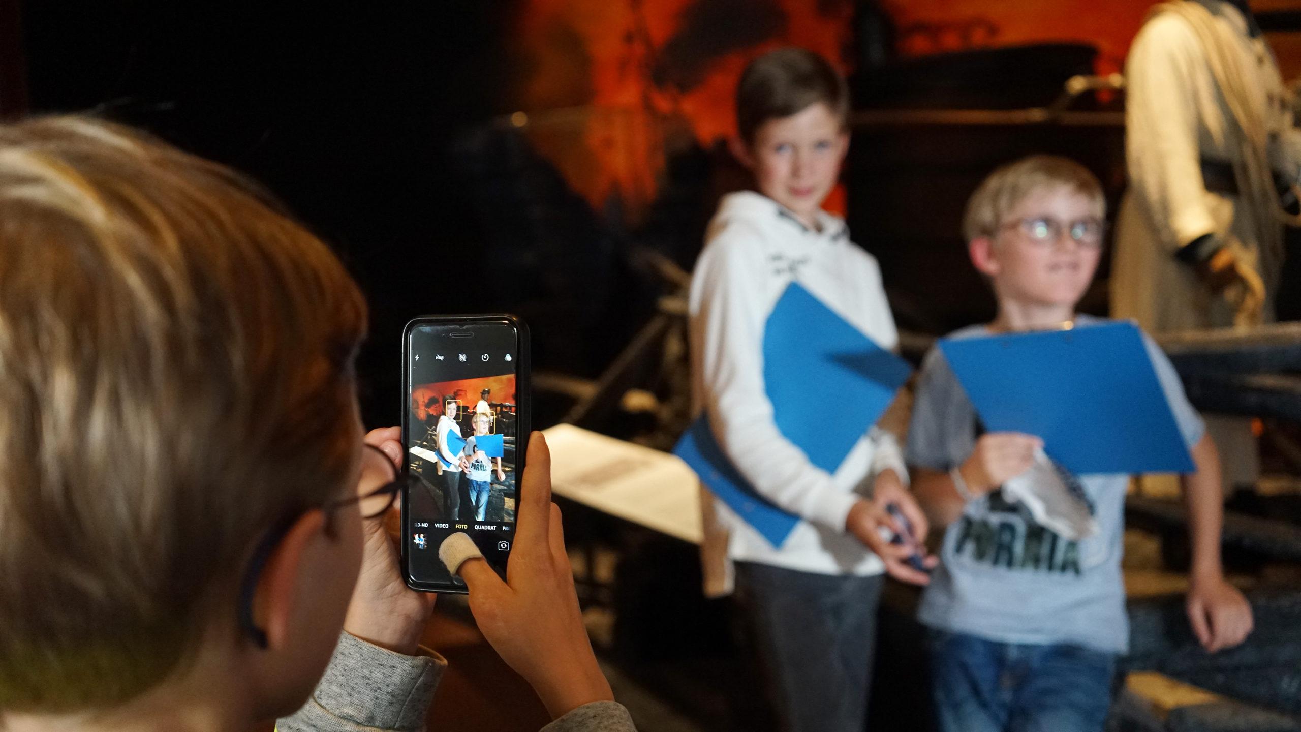Ein Kind fotografiert zwei andere Kinder mit dem Smartphone vor der Rekonstruktion Der Große Brand in Hamburg 1842, Museum für Hamburgische Geschichte