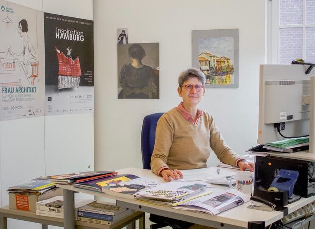 Martina Bergmann sitzt am Tisch in ihrem Büro