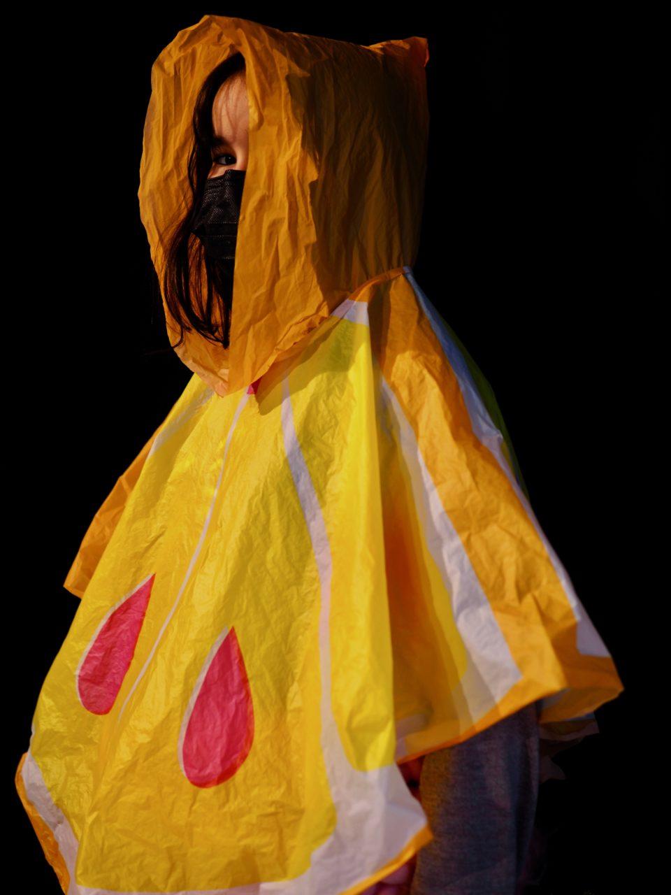 Damla Dolan mit Mundschutz und Regencape gekleidet