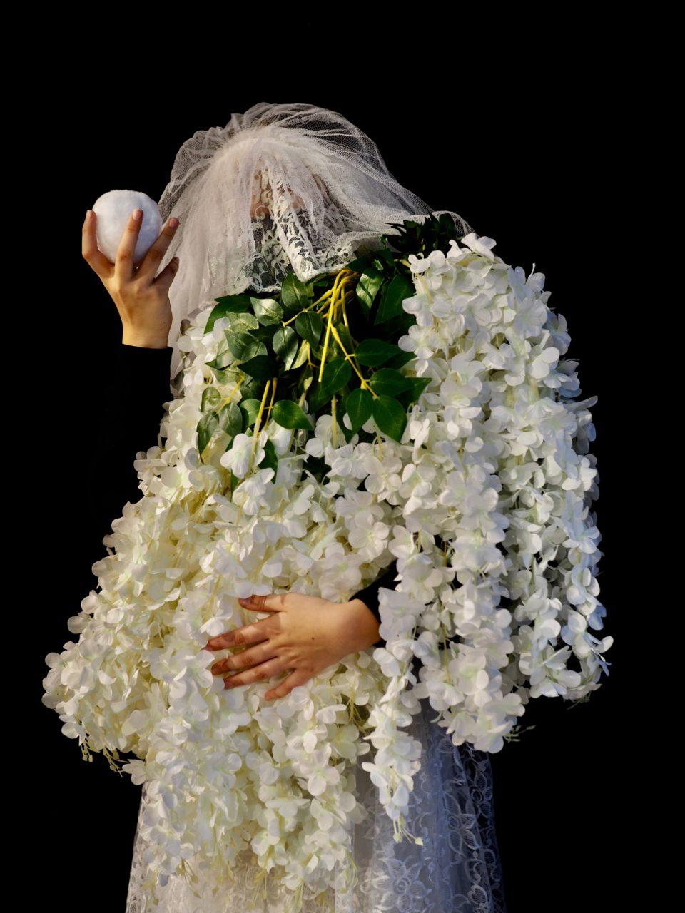 Jemand ist vollständig verschleiert mit künstlichen Pflanzen und einem weißen Gesichtsschleier. Man erkennt nicht, ob Mann, Frau, Mädchen oder Junge. Die Person hält einen kleinen weißen Stoffball in einer Hand hoch wie ein antikes Attribut.