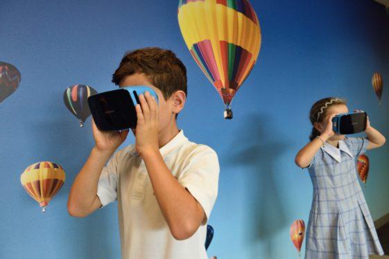 Ein Junge und ein Mädchen schauen durch VR-Brillen. Sie stehen vor einer Fototapete, die einen blauen Himmel mit Heißluftballons zeigt.Himmel