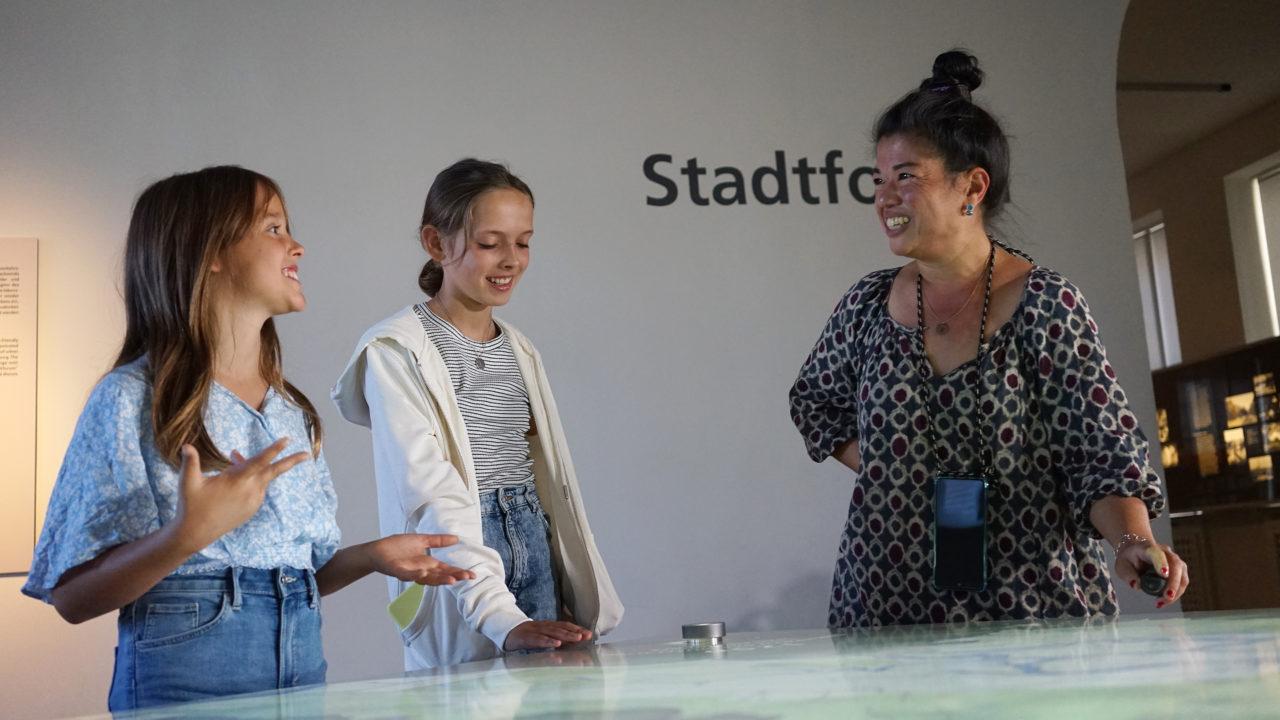 Auf diesem Foto sind zwei Mädchen und ihr Guide zu sehen, die um den Medientisch des Museums für Hamburgische Geschichte stehen. Alle Drei lächeln und unterhalten sich.