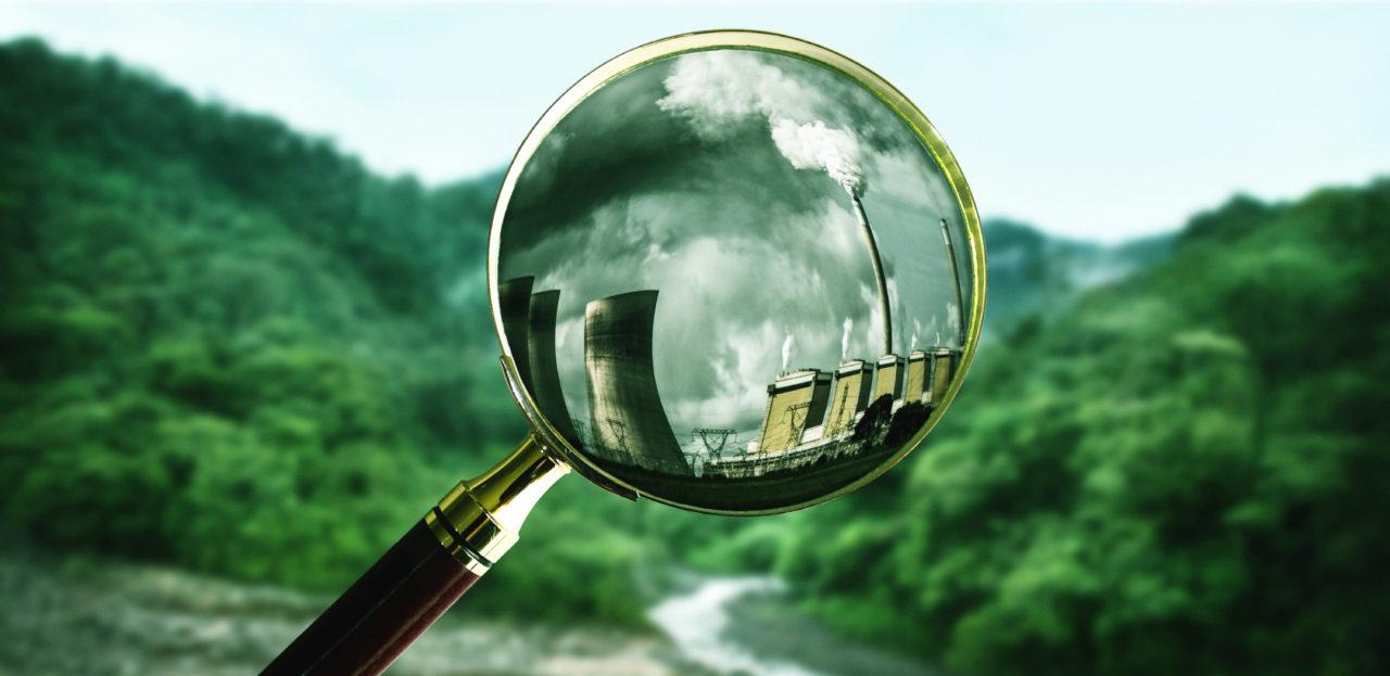 Auf einer grünen Landschaft sind Industriebauten hinter einer Lupe zu sehen