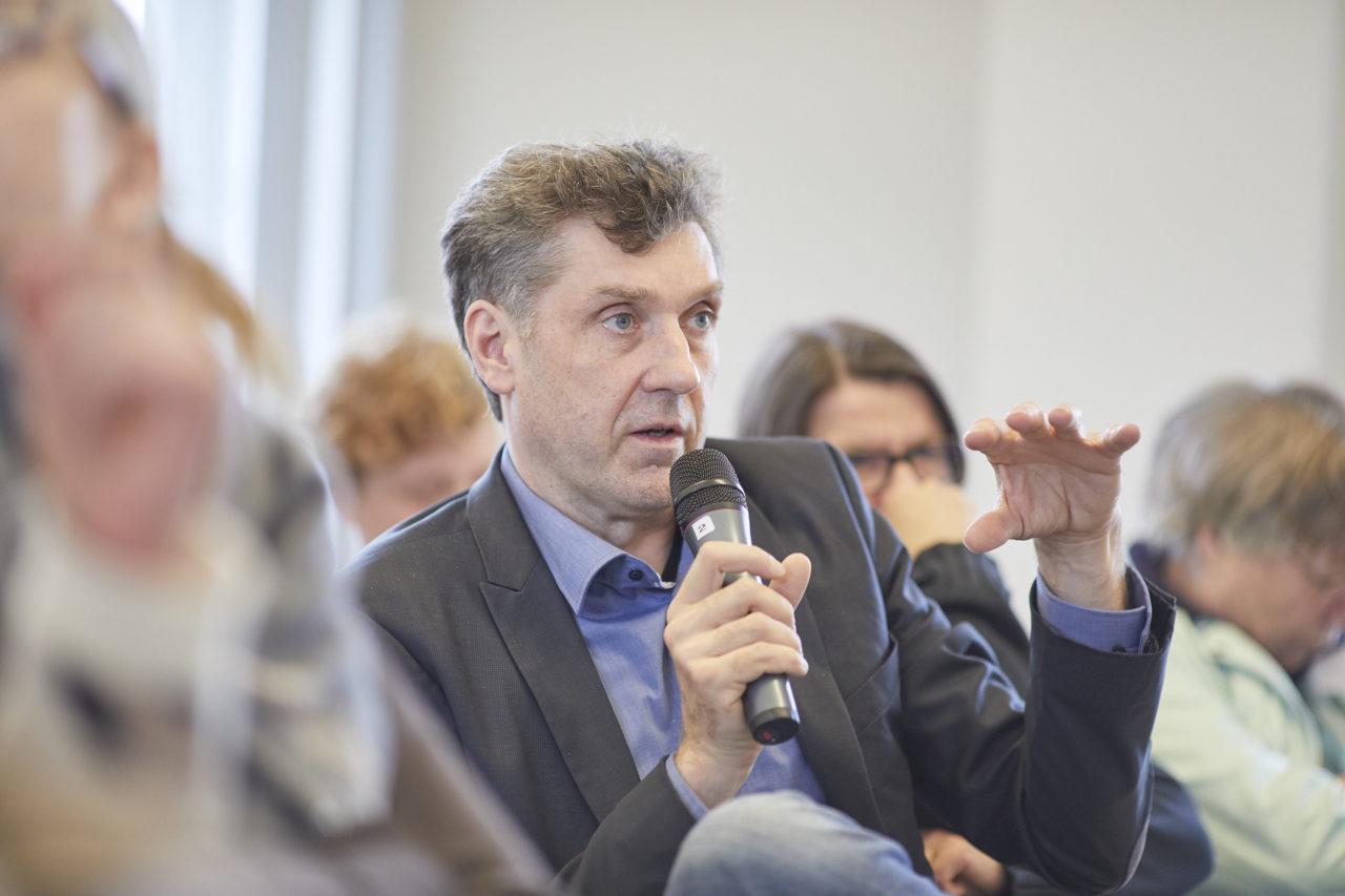 Oliver von Wrochem, Leiter der KZ-Gedenkstätte Neuengamme, spricht bei einer Veranstaltung mit Mikro.