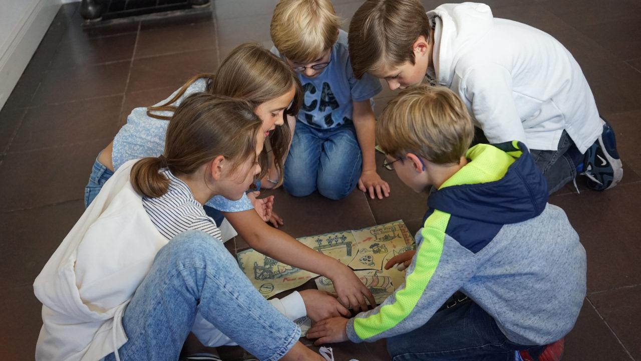 Eine Gruppe Kinder sitzt auf dem Boden. In ihrer Mitte liegen verschiedene Papierstücke, die zusammengesetzt werden.