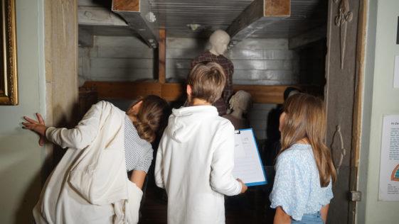 Eine Gruppe Kinder schaut in eine Rekonstruktion zum Thema Auswanderung nach Amerika an. Es ist ein Segelschiff-Zwischendeck dargestellt auf dem mehrere bekleidete Figuren stehen.