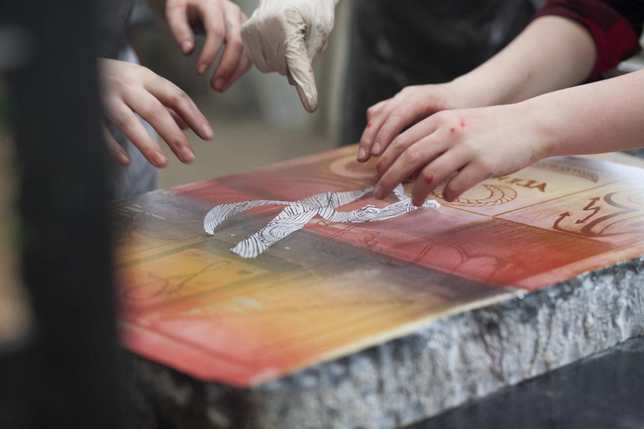 Zwei Hände sind beim Steindruck mit einer orange-gelben Fläche zu sehen.