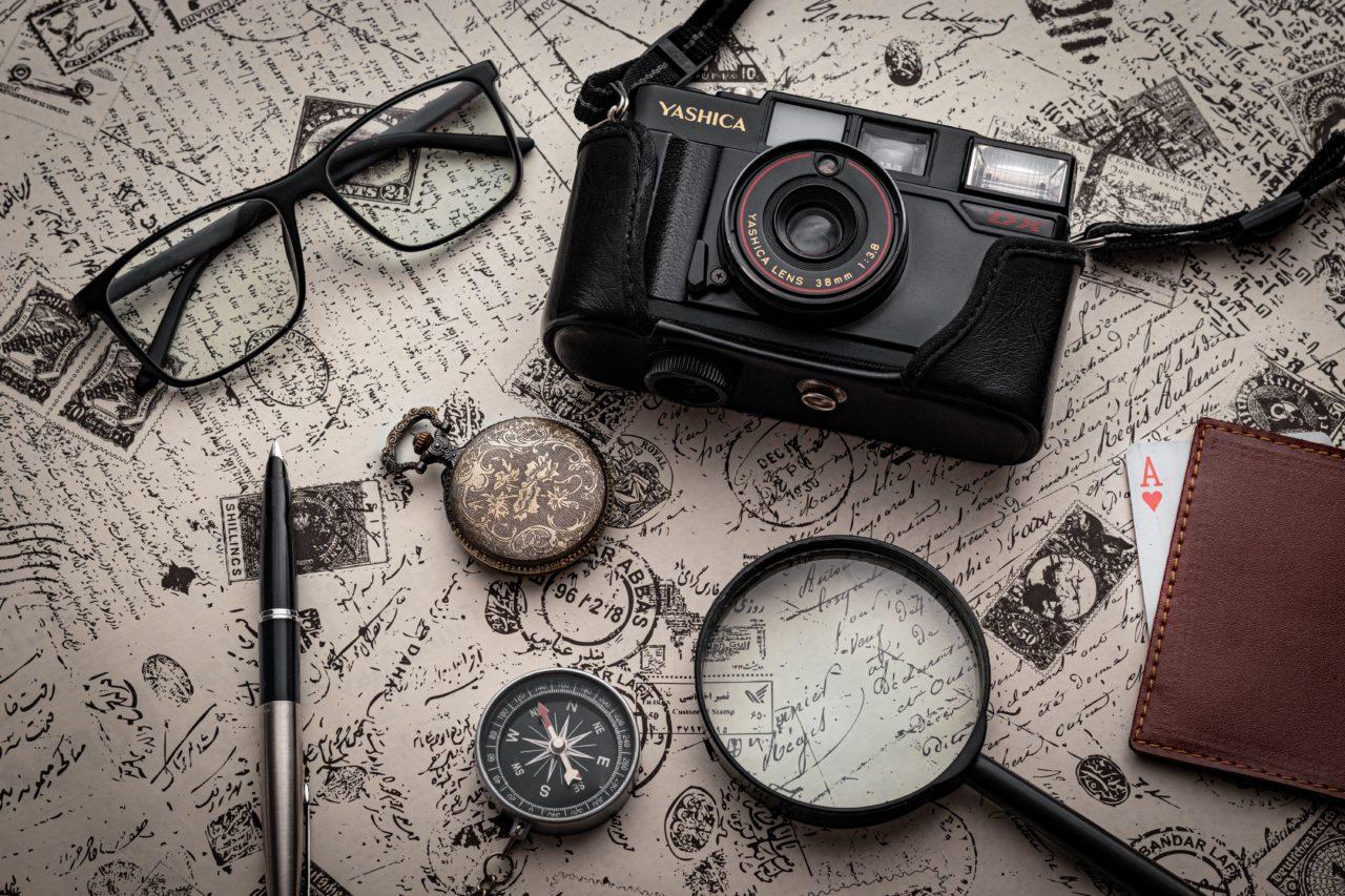 Detektivutensilienn wie Kamera, Brille, Lupe sind großformatig zu sehen auf einem landkartenähnlichen Hintergrund.