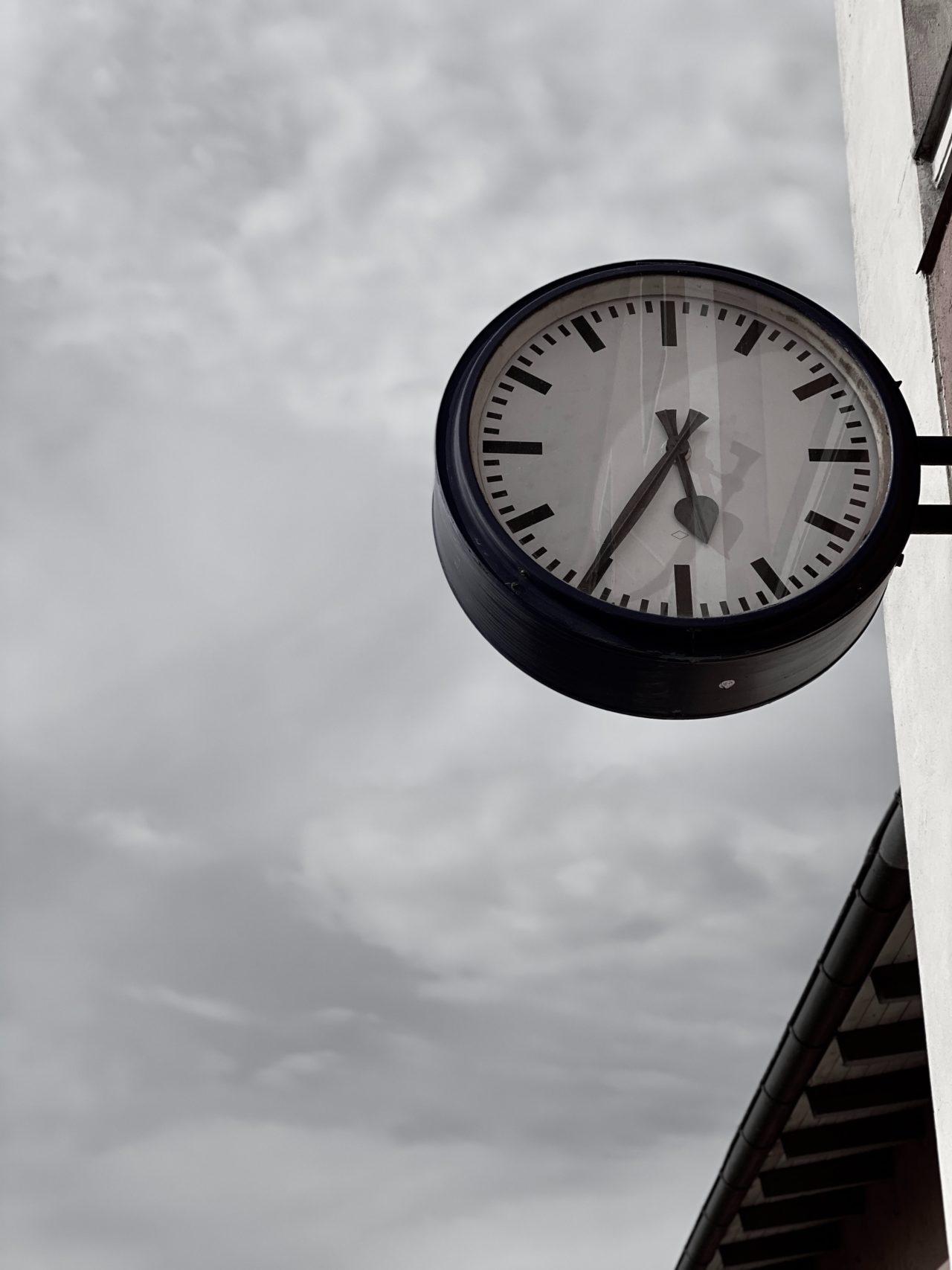 Schwarz-weiß-Fotografie einer Bahnhofsuhr vor wolkigem Himmel.